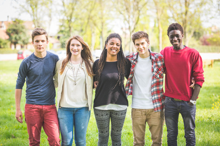 Multi-etnische groep van tieners outdoor. Ze worden omarmd in het park, twee jongens en een meisje zijn Kaukasisch, een jongen en een meisje zijn zwart. Vriendschap, immigratie, integratie en multiculturele concepten.