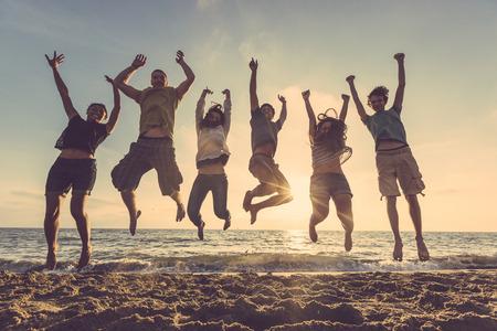 amicizia: Gruppo multietnico di persone che saltano alla spiaggia. Colpo retroilluminazione. Felicità, successo, amicizia e comunità concetti.