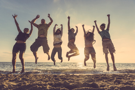 Multiracial group of people jumping at beach. Backlight shot. Happiness, success, friendship and community concepts. photo