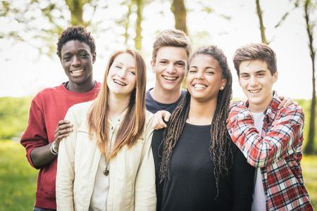 grupo de hombres: Grupo multiétnico de adolescentes al aire libre. Se abrazaron en el parque, dos chicos y una chica son caucásicos, un niño y una niña son de color negro. Amistad, la inmigración, la integración y conceptos multiculturales.