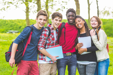 Group of multiethnic teenage students embraced together at park. Two boys and one girl are caucasian, one boy and one girl are black. Friendship, immigration, integration and multicultural concepts. Stock Photo