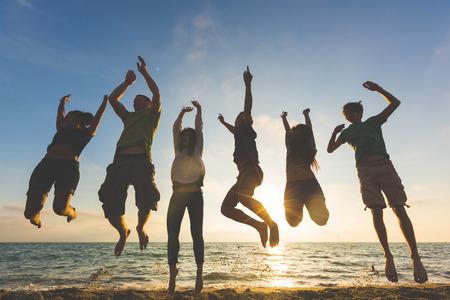 Feiern: Multikulturelle Gruppe von Menschen Springen am Strand. Gegenlichtaufnahme. Glück, Erfolg, Freundschaft und Gemeinschaft Konzepte.
