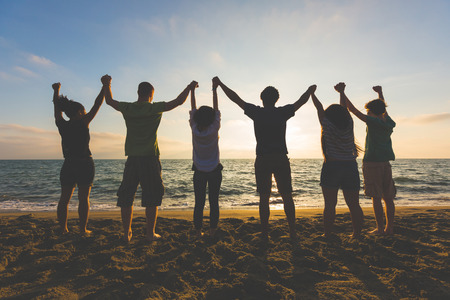 group shot: Multiracial group of people with raised arms looking at sunset. Backlight shot. Happiness, success, friendship and community concepts. Stock Photo