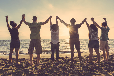 Multiracial group of people with raised arms looking at sunset. Backlight shot. Happiness, success, friendship and community concepts. Stock Photo
