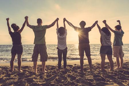Wielorasowe grupy osób z podniesionymi rękami patrząc na zachód słońca. Podświetlenie strzał. Szczęście, sukces, przyjaźń i społeczne koncepcje.