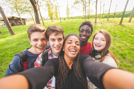 smiling teenagers: Group of multiethnic teenagers taking a selfie at park. Two boys and one girl are caucasian, one boy and one girl are black. Friendship, immigration, integration and multicultural concepts. Stock Photo