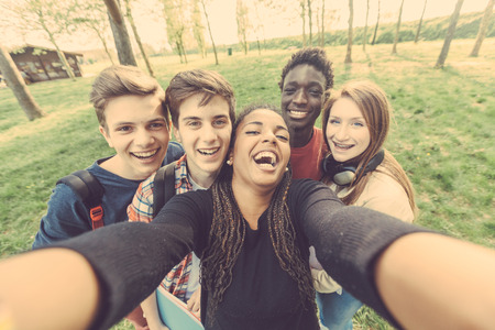 Group of multiethnic teenagers taking a selfie at park. Two boys and one girl are caucasian, one boy and one girl are black. Friendship, immigration, integration and multicultural concepts. Stok Fotoğraf