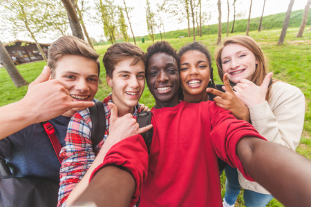Group of multiethnic teenagers taking a selfie at park. Two boys and one girl are caucasian, one boy and one girl are black. Friendship, immigration, integration and multicultural concepts. Banque d'images