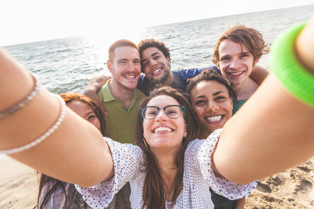 tourism: Multiracial group of friends taking selfie at beach. One girl is asiatic, two persons are black and three are caucasian. Friendship, immigration, integration and summer concepts. Stock Photo