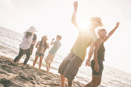 friends: Multiracial group of friends having a party at beach. There are asiatic, black and caucasian persons. Friendship, immigration, integration concepts. Also refers to summer and party.