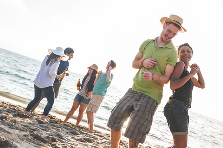 Multiracial group of friends having a party at beach. There are asiatic, black and caucasian persons. Friendship, immigration, integration concepts. Also refers to summer and party. photo