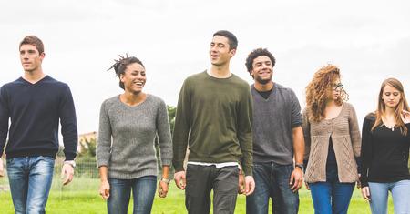 Multi-etnische groep van vrienden in het park te wandelen en te genieten van de tijd samen. Gemengd ras groep met een blanke, zwarte en Aziatische mensen. Vriendschap, lifestyle, immigratie concepten.
