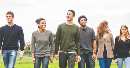 integrate: Multiethnic group of friends at park walking and enjoying time all together. Mixed race group with caucasian, black and asian people. Friendship, lifestyle, immigration concepts. Stock Photo