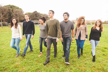 grupo de hombres: Grupo multiétnico de amigos en el parque a pie y disfrutar del tiempo juntos. Grupo de la raza mezclada con la gente caucásica, negros y asiáticos. Conceptos Amistad, estilo de vida, de inmigración.