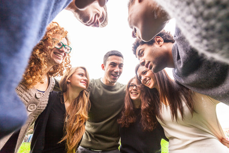 Multiracial group of friends embraced in a circle, strong concept about teamwork and cooperation, also refers to immigration and friendship.