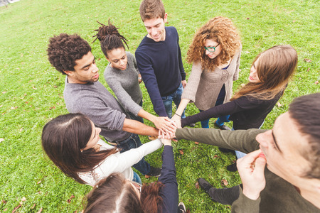 refers: Multiracial group of friends with hands in stack, strong concept about teamwork and cooperation, also refers to immigration and friendship.