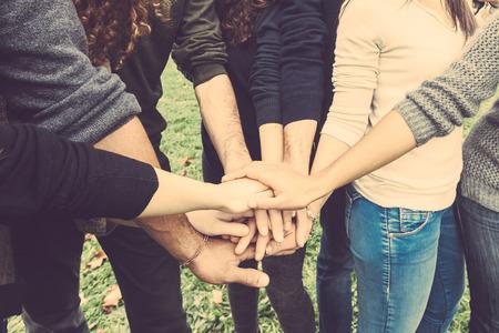amicizia: Gruppo multietnico di amici con le mani in pila, forte concetto di lavoro di squadra e la cooperazione, si riferisce anche l'immigrazione e l'amicizia.