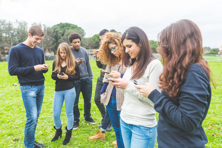 social issues: Multiethnic group of friends looking at their own smart phone. Technology, internet and social network addicion concepts, modern social issues. Stock Photo