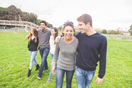 integrated groups: Multiethnic group of friends at park walking and enjoying time all together. Mixed race group with caucasian, black and asian people. Friendship, lifestyle, immigration concepts. Stock Photo
