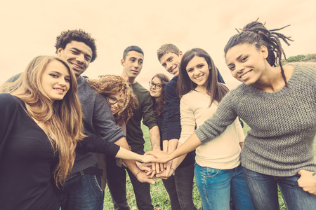juventud: Grupo multirracial de amigos con las manos en la pila, fuerte concepto de trabajo en equipo y la cooperación, también se refiere a la inmigración y la amistad.