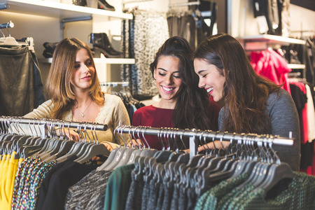 Three women in a clothing store choosing a dress. Girls are on their early twenties, they are happy about shopping, consumerism concept.