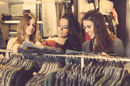 early twenties: Three women in a clothing store choosing a dress. Girls are on their early twenties, they are happy about shopping, consumerism concept.