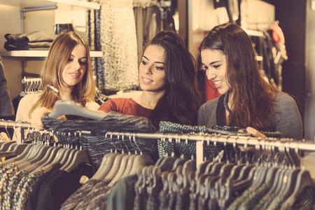 comprando zapatos: Tres mujeres en una tienda de ropa que eligen un vestido. Las niñas están en sus veinte años, están contentos acerca de las compras, el concepto de consumismo. Foto de archivo
