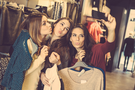 Three women taking a selfie while shopping in a clothing store. They are happy and smiling at camera. Shopping concept, also related to social media addiction. Stockfoto