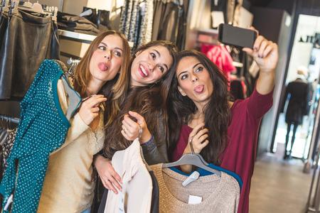 의류 매장에서 쇼핑하는 동안 selfie을 복용 세 여성. 그들은 행복과 미소를 카메라입니다. 또한 소셜 미디어 중독 관련 쇼핑 개념. 스톡 콘텐츠