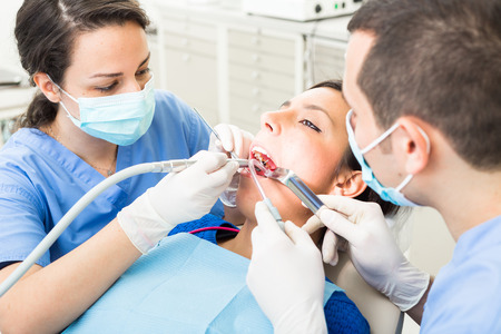 Dentist and dental assistant examining patient teeth. Dentist and Patient are Women, Assistant is a Man. Patient is Relaxed and not scared of Dentist.