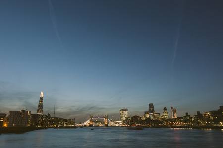 walkie talkie: London skyline at dusk with River Thames on foreground. From left to right The Shard, Tower Bridge, Walkie Talkie and other skyscrapers. All buildings have lights on.