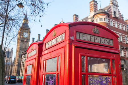 phonebox: Famous red telephone box with Big Ben on background in a sunny early morningin London. There are also some chimneys and trees.