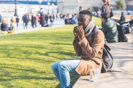 english ethnicity: Young man having lunch break in London next to Tower Bridge. He is seated on a concrete low wall and is eating a sandwich.