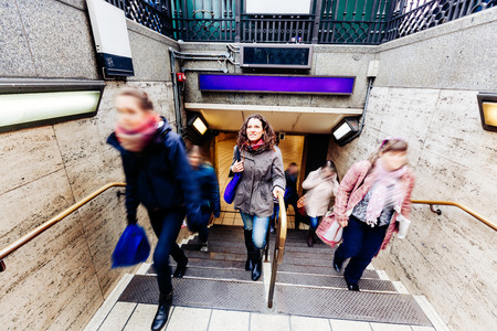 woman stairs: Beautiful caucasian young woman at tube exit in London with blurred people around on the stairs. She is looking up and wearing winter clothes.