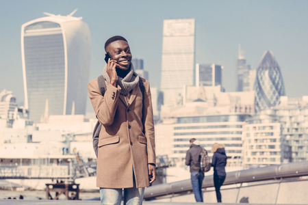 english ethnicity: Young black man talking on mobile phone in London with city skyscrapers on background in a sunny day.