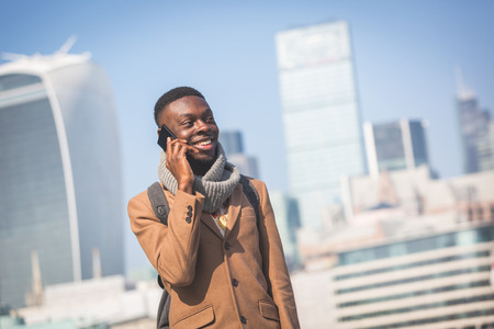 Young black man talking on mobile phone in London with city skyscrapers on background in a sunny day. He is wearing a coat and has a vintage backpack.