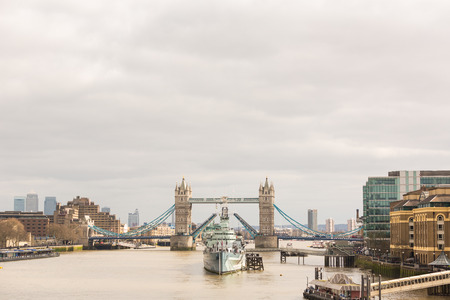 positioned: Tower Bridge in London with drawbridge open on a cloudy day. In foreground there is a battleship positioned in the centre of the bridge. Stock Photo