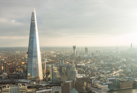 aerial: Aerial view of London with The Shard skyscraper and Thames river at sunset with grey clouds in the sky Stock Photo
