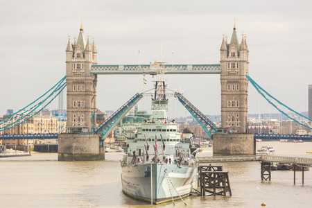 drawbridge: Tower Bridge in London with drawbridge open on a cloudy day. In foreground there is a battleship positioned in the centre of the bridge. Stock Photo