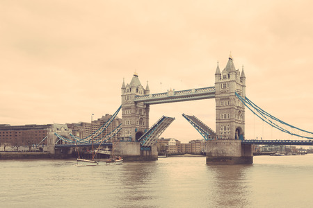 drawbridge: Tower Bridge in London with drawbridge open on a cloudy day with a sail passing through. Stock Photo
