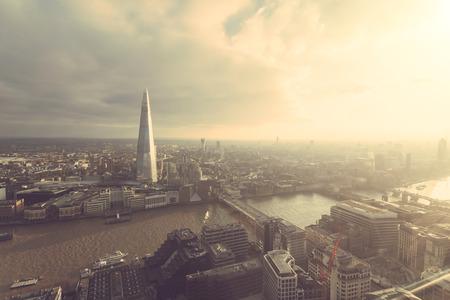 aerial: Vista aérea de Londres con El rascacielos Fragmento y el río Támesis al atardecer con nubes grises en el cielo