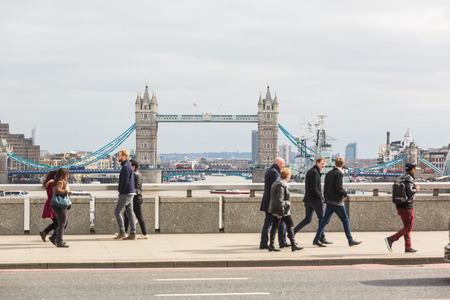 hms: LONDON, UNITED KINGDOM - MARCH 22, 2015: People, most of which tourists, walking on London Bridge, with Tower Bridge and HMS Belfast on background. Focus on the Bridge. Editorial