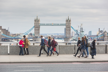 hms: LONDON, UNITED KINGDOM - MARCH 22, 2015: People, most of which tourists, walking on London Bridge, with Tower Bridge and HMS Belfast on background.