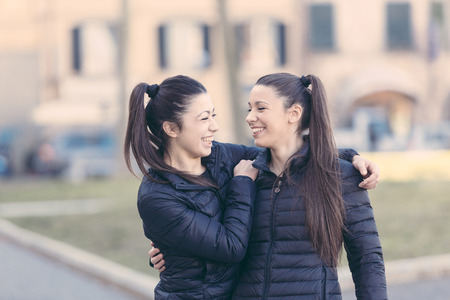 Female Twins Playing together and Enjoy Getting Piggyback Ride. They are Smiling and Looking Each Other. They wear Similar Clothes and they both Have Ponytail Hair.