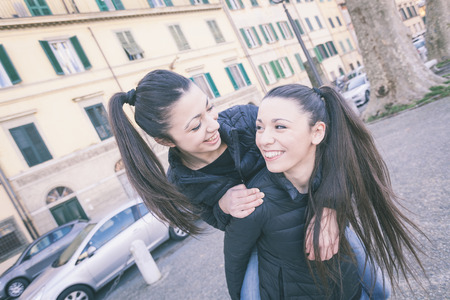 teen couple: Female Twins Playing together and Enjoy Getting Piggyback Ride. They are Smiling and Looking Each Other. They wear Similar Clothes and they both Have Ponytail Hair.