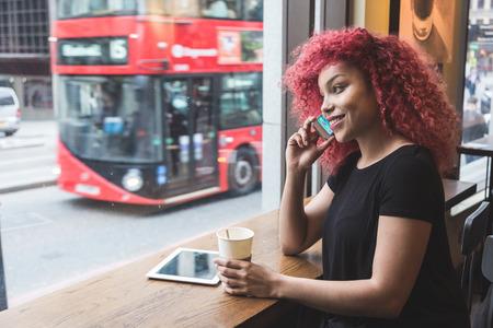 modelos negras: Hermosa chica con el pelo rojo rizado hablando por tel�fono inteligente en un caf�. Tambi�n ella es la celebraci�n de una taza de caf� y ella tiene una tableta digital en la mesa.