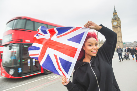 english girl: Beautiful redhair woman holding United Kingdom flag, also known as Union Jack, in London with Big Beg and Westminster palace on background. Stock Photo