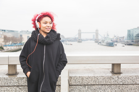 mixed race woman: Beautiful redhair woman listening music in London with Tower Bridge on background. She wear a black jacket and fashion white headphones.