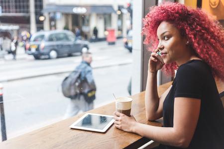 personas sentadas: Hermosa chica con el pelo rojo rizado hablando por tel�fono inteligente en un caf�. Tambi�n ella es la celebraci�n de una taza de caf� y ella tiene una tableta digital en la mesa.