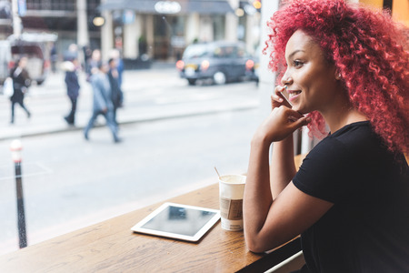 Beautiful girl with curly red hair talking on smart phone in a cafe. Also she is holding a cup of coffee and she has a digital tablet on the table. Foto de archivo